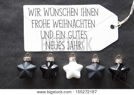 Label With German Text Wir Wuenschen Frohe Weihnachten Und Ein Gutes Neues Jahr Means Merry Christmas And Happy New Year. Black And White Christmas Tree Balls On Black Paper Background.