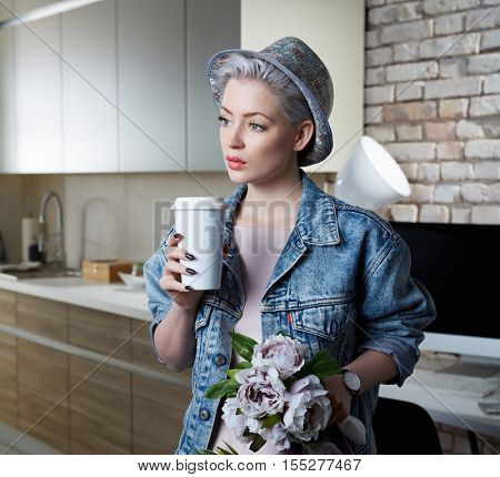 Daydreaming young woman standing at home in kitchen, drinking coffee. Just arrived home.