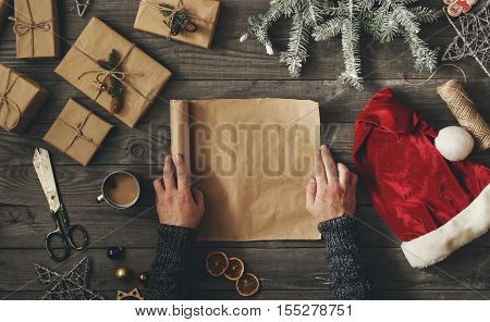 Men hands holds blank sheet of paper on dark wooden table with Christmas gift overhead view