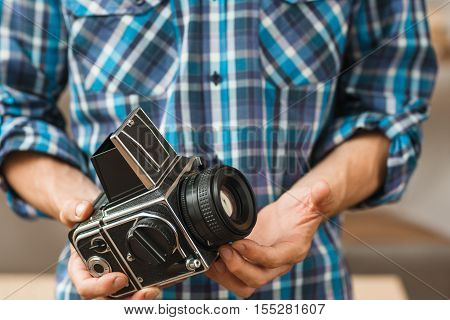 Professional retro photo camera presentation. Unrecognizable photographer holding old fashioned photographing equipment, free space , bright blue background