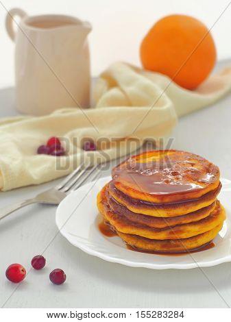 Pumpkin pancakes with caramel sause and cranberries. Fresh homemade flapjacks. Thanksgiving treat.