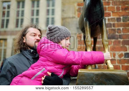 BREMEN GERMANY - MARCH 23 2016: Little tourist touching famous statue in the center of Bremen known as Bremen Town Musicians which supposed to bring good luck