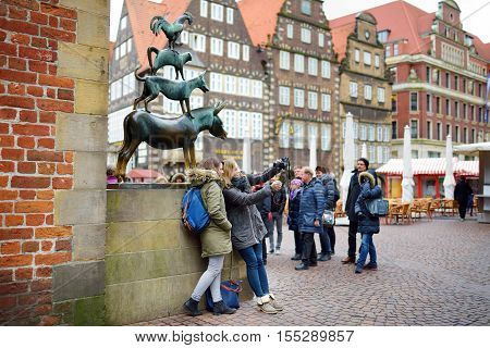 BREMEN GERMANY - MARCH 23 2016: Tourists taking pictures of themselves by famous statue in the center of Bremen depicting the donkey dog cat and cockerel from Grimm's famous fairy tale The Bremen Town Musicians