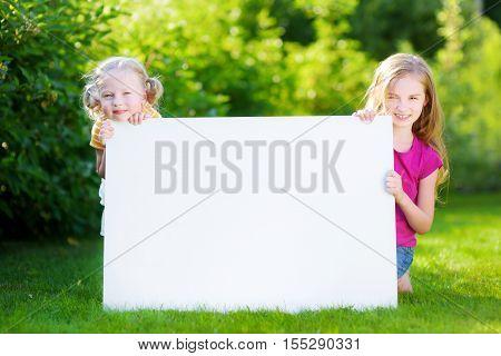Two Cute Little Sisters Holding Big Blank Whiteboard