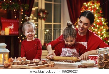 Merry Christmas and Happy Holidays. Family preparation holiday food. Mother and daughters cooking Christmas cookies.