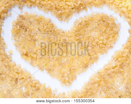 Background of heart-shaped bulgur. Top view or flat lay. Healthy food and diet concept