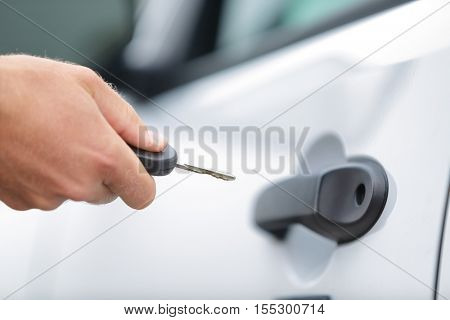 Man opening unlocking door with car key. Car keys closeup of hand holding key to lock or unlock doors of white car travel vacation rental or driver owning new car.