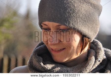 Beautiful and smiling woman in a cap and scarf.
