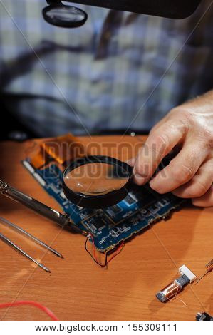 Male electrician soldering computer board checking detail with magnifier. Closeup of male hands.