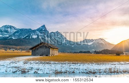 Alpine scenery at  winter sundown - Winter alpine landscape with an aged wooden barn the Alps mountains a frozen river at sundown. Picture captured in Austria.