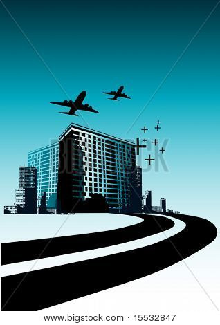 Highway leading into a city with buildings and planes.