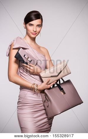 Beautiful glamour woman with jewelry and bag in elegant dress. Fashion girl deciding between clutch bag and purse isolated on grey backgound. Elegant woman with choosing her bag from many purses.