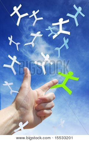 A hand pointing to a paper man falling from the sky