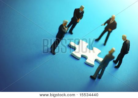 A business team around a puzzle piece.