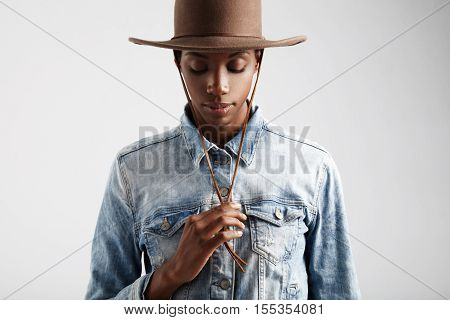 black woman in cowboy hat watching down
