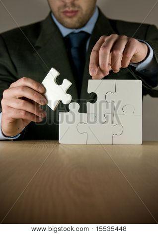 Ein Geschäftsmann, eine Puzzle machen.
