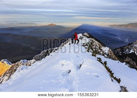 Mountain summit and distant hiker standing and watching the sunset in winter
