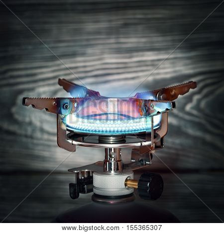 The burning portable gas burner on wooden background