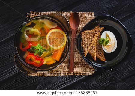 Fresh vegetable soup in a pot on the black wooden background