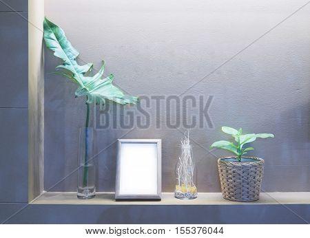 Flowerpot picture frame and vase on built in shelf under down light.