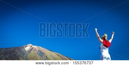 Happy celebrating winning success woman standing elated with arms raised up above her head in celebration of having reached mountain.