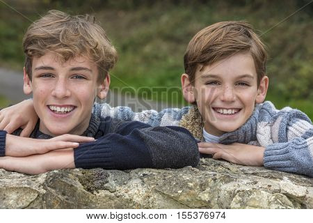 Happy boy children brothers smiling together outside leaning on a wall