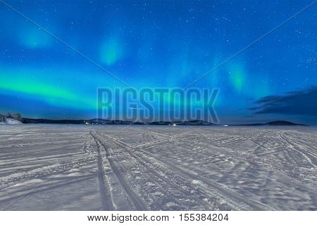 Northern lights glow above a frozen lake in Lapland