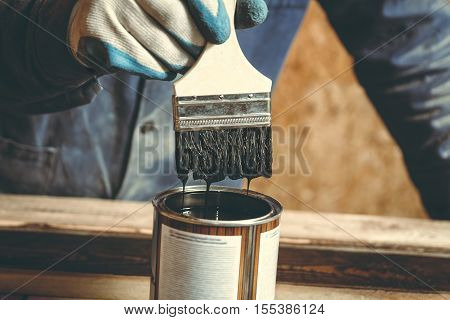 Man carpenter color brown paint wooden plank in his home workshop. Close-up brush with paint drops