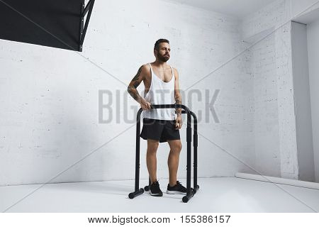 Brutal tattooed bearded male athlete in blank white tank t-shirt standing next to parallel bars and pull bar looking on side , ready to workout, looking on side