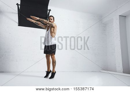 Strong tattooed in white unlabeled tank t-shirt male athlete shows calisthenic moves Squat calf rises