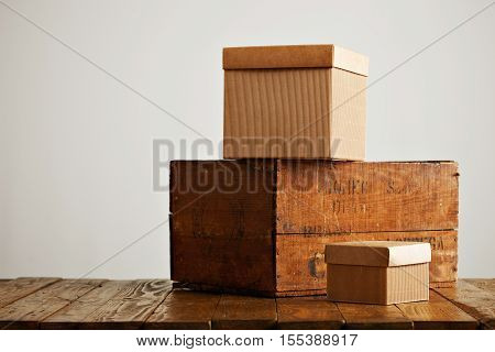 Unlabeled cardboard boxes with covers presented next to an old brown wine crate in a studio with white walls