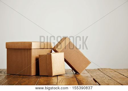 Unlabeled packaging boxes with covers on top of a rustic wooden table isolated on white