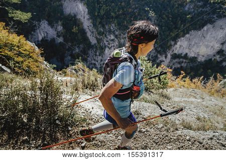 Yalta Russia - October 6 2016: closeup young woman runner with walking poles running steep cliff during Crimea mountain marathon