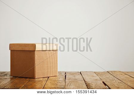 New fancy square corrugated cardboard box with a cover shot on top of a beautiful rustic table in a studio with white walls