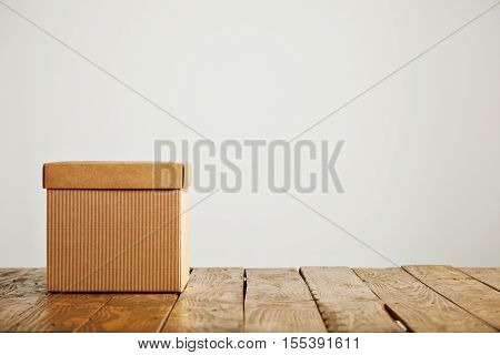 Front shot of an unlabeled square beige cardboard box with cover on wooden floor isolated on white