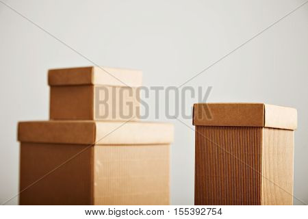 Blank unlabeled brown corrugated cardboard boxes with covers arranged in a beautiful composition isolated on white
