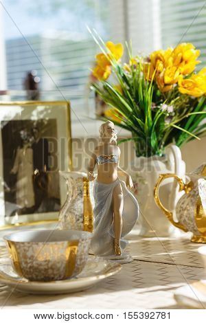 Ballerina figurine at the table with Cup of tea summer flowers and old photo