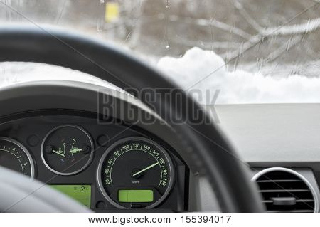 Car speedometer and a windshield covered with ice and snow. Closeup with particular focus