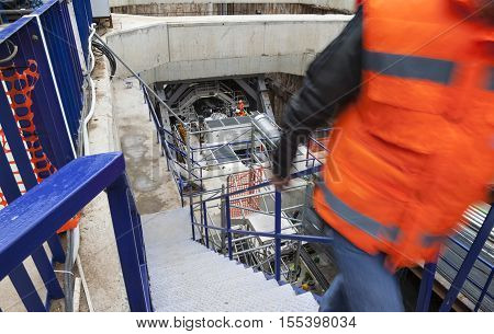 A construction site of an underground with a huge drilling machine at the entrance of a tunnel.