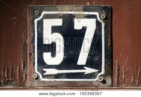 Weathered grunge square metal enameled plate of number of street address with number 57 closeup