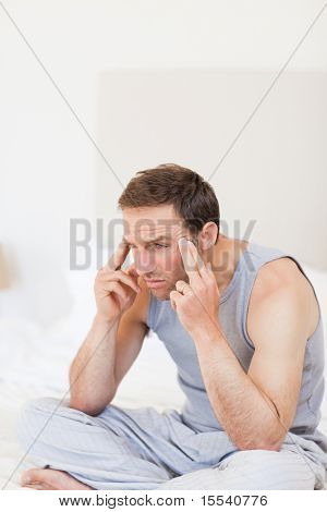 Thoughtful man sitting on his bed