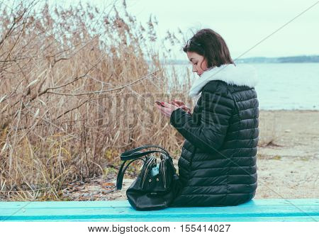 Girl with phone sitting on the aprk ebanch in autumn time