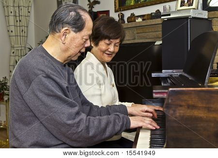 Senior Couple Playing The Piano