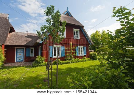 old fisherman's cottage with thatched roof and pretty garden