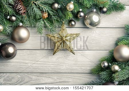 Christmas background with bright wooden board and fir branches decorated with silver baubles and a gold star - modern simple and elegant