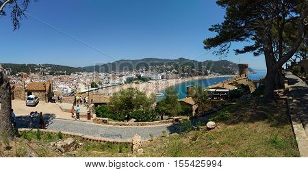 TOSSA DE MAR, CATLONIA, SPAIN - JUNE 19: Resort vacationers are visiting town, Gran beach and fortress Vila Vella Enceinte on June 19, 2014 in Tossa de Mar, Costa Brava, Catalonia, Spain.