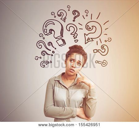 Portrait of African American woman standing near gray wall with multiple question marks drawn on it. Concept of question. Toned image