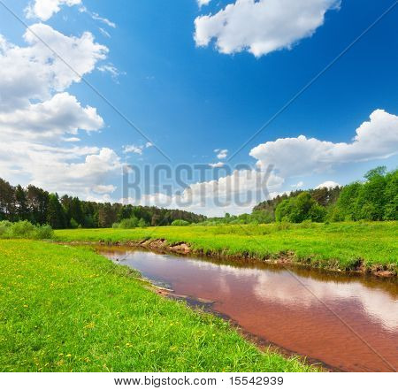 Green field and river under blue sky