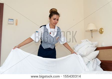 MOSCOW - OCTOBER 31: Young and beautiful maid girl spreading bed at room in Izmaylovo hotel on October 31 2016 in Moscow. Izmailovo Hotel is four-building hotel located in Izmaylovo District of Moscow.