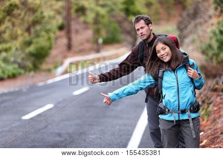 Travel hikers couple showing thumbs up on street for hitchhiking during road trip. Happy young interracial backpackers hitchhikers waiting for a rideshare, sharing a ride on vacation holidays.